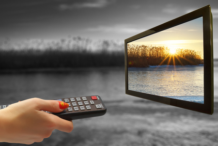girl hand switches TV channels. Nature. Abstract. remote control in hand and TV