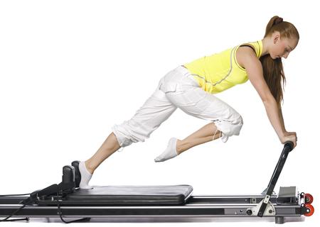 allegro: Fitness girl doing pilates on the allegro. Isolated on white