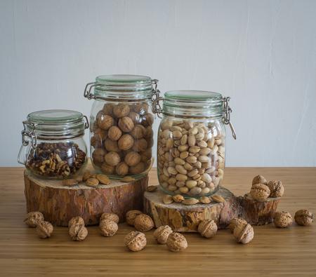 apricot kernel: walnuts, Peeled walnuts, pistachios, Brasil nuts in glass jar on wooden stand Stock Photo