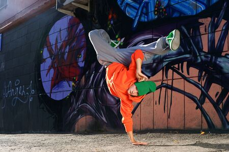 urban street: boy dancing on the street graffity wall Stock Photo
