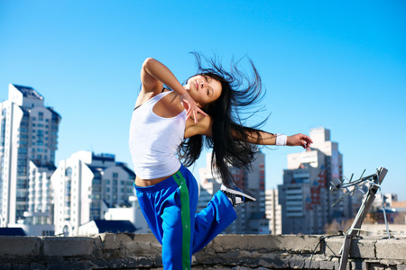fitness dancing girl on the roof blue sky