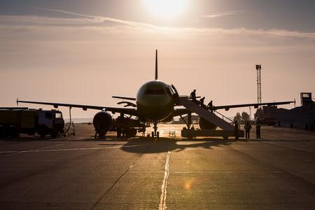 crew: captain and crew disembark airplane sunset sky