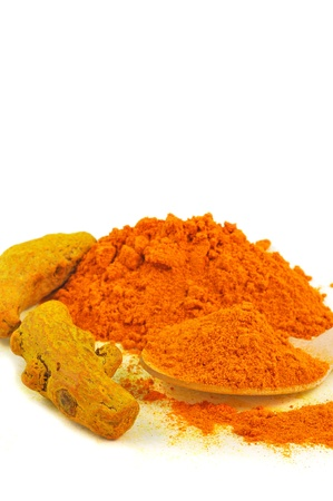 close up of powder and whole turmeric