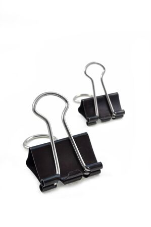 close up of black binder clips arranged on white