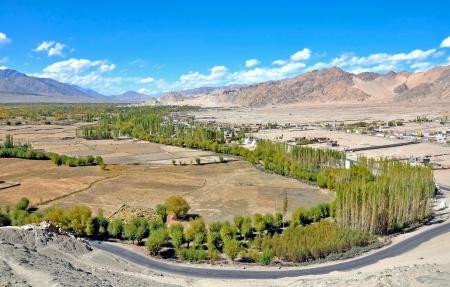 human settlement: vast view of barren mountain valley with human settlement