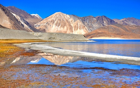 reflection of barren mountains in lake