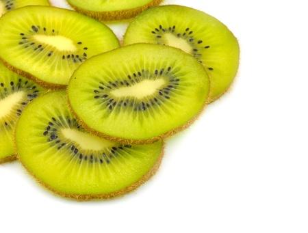 close up of slices of kiwifruits arranged on white