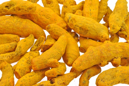 close up of turmeric roots scattered on white background Stock Photo