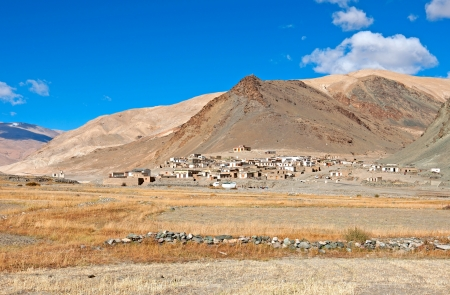 wide shot of barren mountains in Ladakh with a patch of houses on hill slope