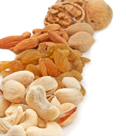 close up of varities of dry fruits piled on white