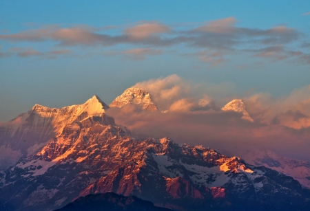 devi: clouds partially covering mountain peak during sunset