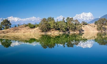 lake reflecting snow clad peak and forest himalaya Stock Photo