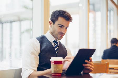 hombre tomando cafe: Hombre de negocios usando una tableta digital Foto de archivo