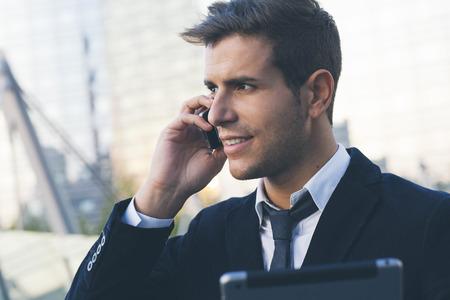 Zakenman met behulp van een mobiele telefoon en digitale tablet