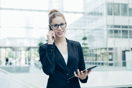 20 s: Businesswoman using a mobile phone Stock Photo