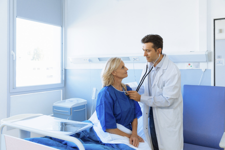 hospital patient: Doctor examining senior patient in hospital Stock Photo