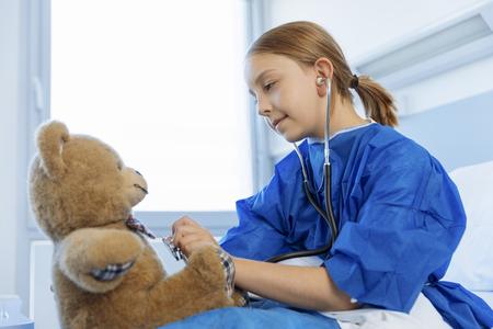 a medical examination: Little girl Examining her Teddy bear in hospital Stock Photo