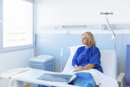 woman alone: Portrait of a  senior looking out of the window in hospital