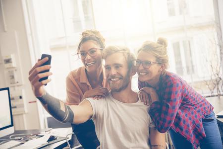Vrienden op het werk die zelfportret met camera telefoon