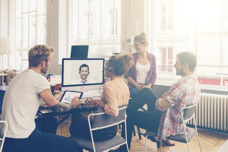 Compañeros de trabajo haciendo una videoconferencia en la sala de conferencias Foto de archivo - 68449999