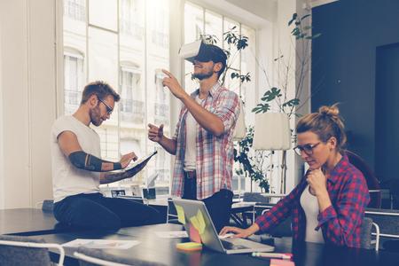 Los empresarios de prueba de tecnología de realidad virtual con su colega en la oficina. Foto de archivo