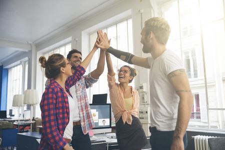 Lachende jonge ondernemers vieren een succes