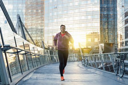 escucha activa: Atleta con auriculares corriendo en la ciudad