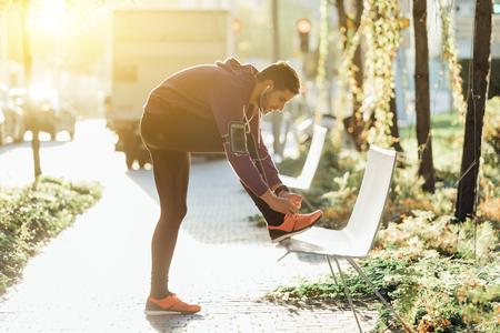 Mannelijke atleet koppelen schoenveters op de bank Stockfoto