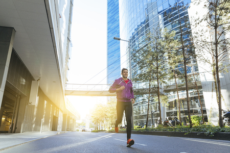 athlete with earphones running in the city