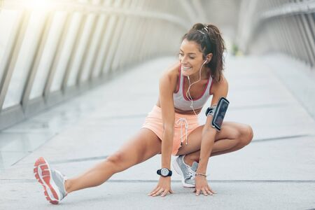 woman stretching: young fitness woman runner stretching legs before run