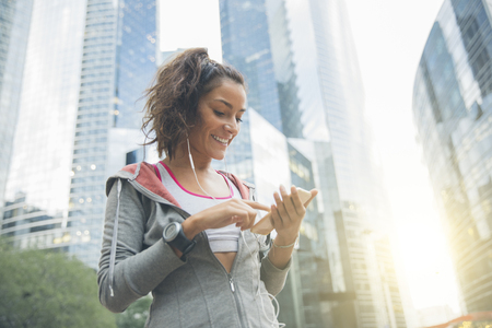 Young woman runner wearing armband and listening to music on earphones