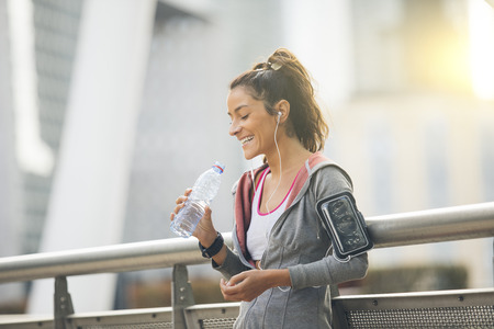 cellular: Woman runner is having a break and drinking water Stock Photo