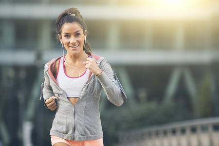 woman running: Young woman running in the city street Stock Photo
