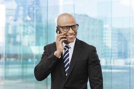 Afro Amerikaanse zakenman die op mobiele telefoon spreekt Stockfoto