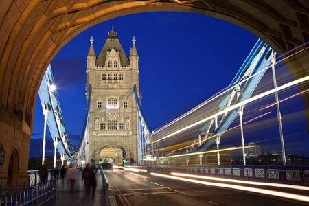 Traffic on the Tower Bridge illuminated at dusk in London, England.