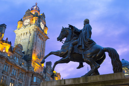 Statue of Wellington on horseback silhouetted against a blue sky, with the clock tower of Balmoral Hotel in the background
