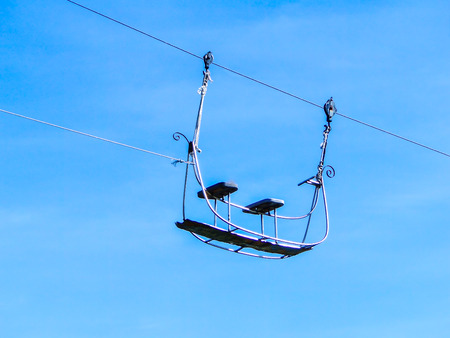 A silhouette of air-cable car isolated on blue background.