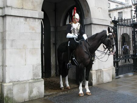 London, United Kingdom – July 03, 2008: A cavalryman of the Blues and Royals cavalry regiment on duty at the entrance to the Horse Guards in the Central London. Urban scene on a summer day.