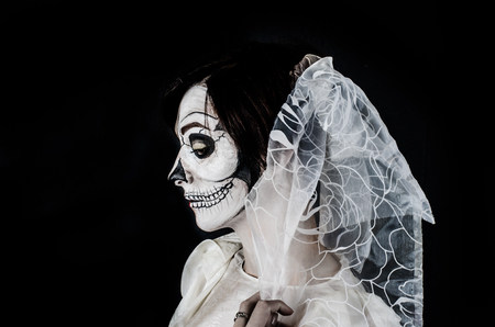 terrifying: Young woman in day of the dead mask skull face art.