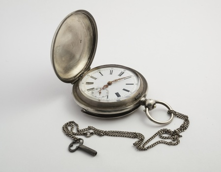 Antique pocket watch in silver with small key on a light background. Appearance with the lid open. Stock Photo - 18425042