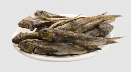 bullhead fish: Dried gobies on a white plate close-up. Isolated on a light gray background. Stock Photo