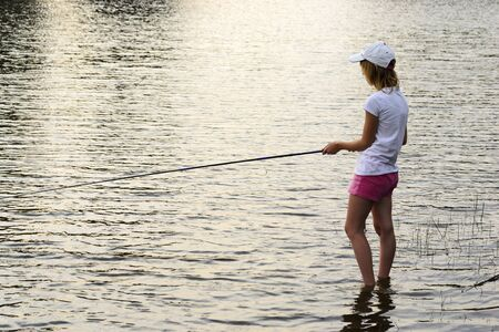 Girl fishing in a lake photo