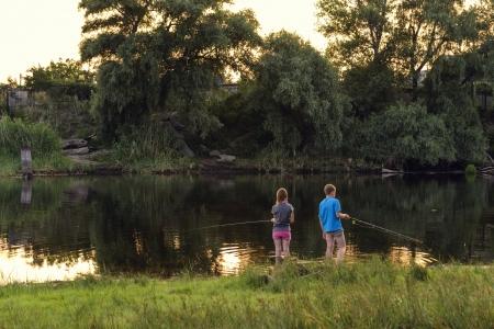 Boy and girl fishing on a lake