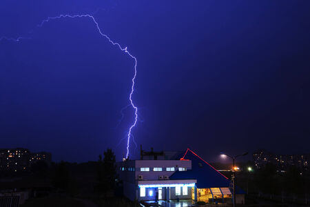 Severe lightning storm with rain over a city buildings at night photo