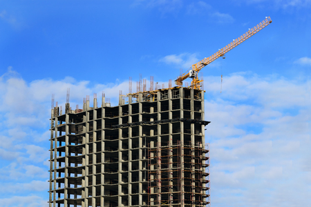 Top part of high-rise modern building under construction and crane against the blue cloudy sky photo