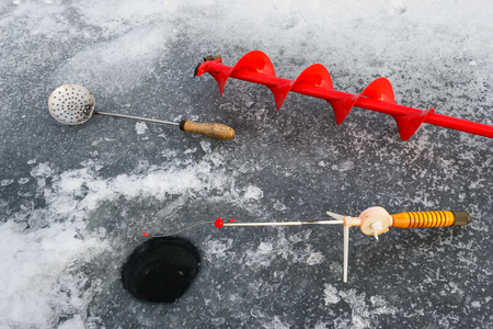 boer: Fishing tackle for ice fishing such as the boer and the fishing rod near the ice-hole on ice Stock Photo
