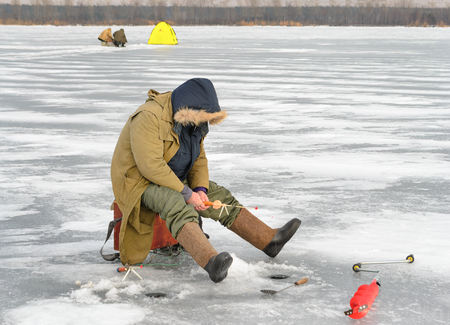 boer: Fisherman catching a fish on the ice fishing