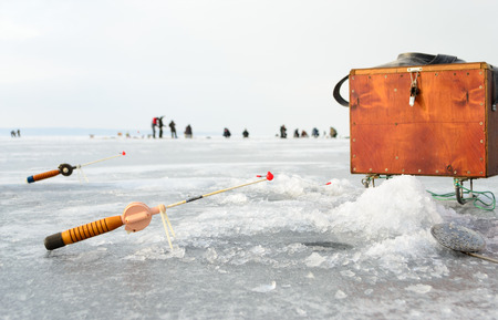 boer: Fishing tackle for ice fishing such as a fishing rod and box near the ice-hole on ice