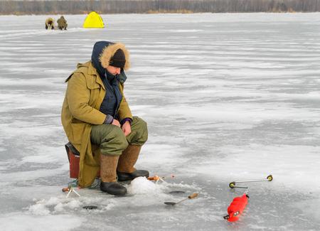 ice fishing: Fisherman catching fish on ice fishing Stock Photo