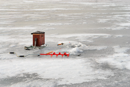 boer: Fishing tackle for ice fishing such as a boer, fishing rod and box near ice-hole on ice Stock Photo